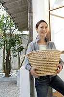 View of a young woman holding a basket