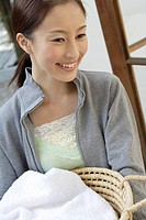 View of a young woman holding a basket (thumbnail)