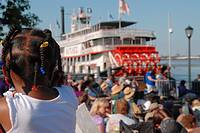 Black girl observing the Natchez steamboat on the Mississippi riverside, New Orleans, Louisiana, USA