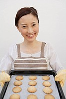 Portrait of a woman holding tray of biscuits