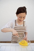 View of a young woman mixing eggs yolks with whisk