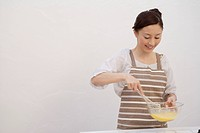 View of a young woman mixing egg yolk with whisk