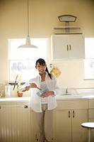 A young woman holding spatula and bowl in kitchen