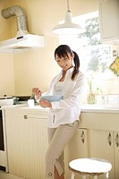 A young woman holding spatula and bowl in kitchen (thumbnail)