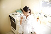 Young woman drinking cup of coffee in kitchen (thumbnail)