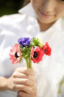 Woman with flowers in foreground (thumbnail)