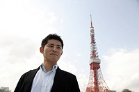 Low angle view of a young man with tower in background