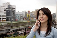 View of a smiling young woman using mobile phone