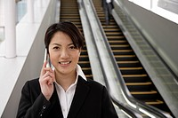 Portrait of a smiling young woman using mobile phone on the moving stairway