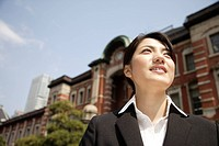 Low angle view of a smiling young woman standing outside the building