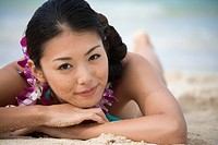 Portrait of a young woman lying at beach