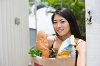A young woman holding paper bag with groceries (thumbnail)