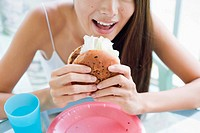 A young woman eating burger