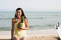 Portrait of a young woman holding pineapple