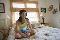 A woman listening to music on bed