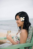 A woman holding wineglass at beach