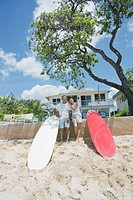 A couple together standing with surfboards