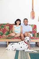 A couple sitting on sofa with dog