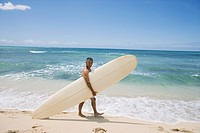 Mature man walking with surfboard at beach