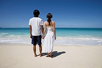 Rear view of a young couple holding hands at beach