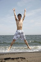 Portrait of a young man jumping on beach