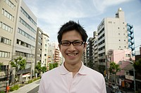 Portrait of a young man smiling with buildings in background