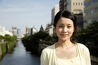 Portrait of a young woman smiling with canal in background