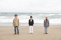 Young man standing with father and grandfather at beach