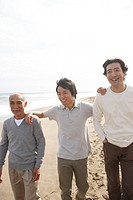 Young man with father and grandfather at beach