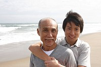 Grandfather with grandson at beach, portrait (thumbnail)