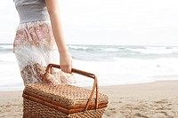 Teenage girl 14-15 with picnic basket at beach, midsection (thumbnail)