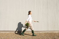 Teenage girl 14-15 walking with shovel and potted plant (thumbnail)