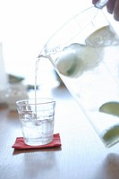Person pouring water in glass, close_up
