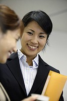 A woman holding a file shares a happy moment with her colleague