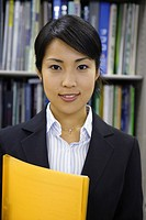 A woman holding a file smiles at the camera