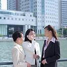 Businesswoman talking on a mobile phone standing beside two businesswomen