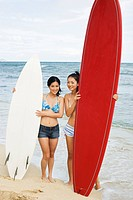Young women standing with surfboards at beach