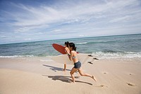 Profile of young women running with surfboards at beach