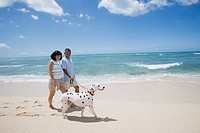 Husband and wife walking with dog on beach