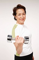 Senior woman holding dumbbell, portrait
