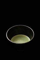 Matcha Japanese powdered green tea against black background, close_up