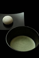 Matcha Japanese powdered green tea and tea whisk against black background, close_up