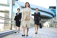 Japan, Honshu, Tokyo, Businesswomen walking on bridge, smiling