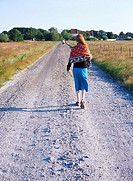 A woman walking on a country road Sweden.