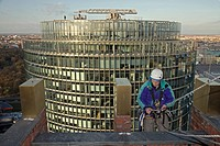 industrial climber working on Kollhoff_Tower with DB tower in background, Berlin