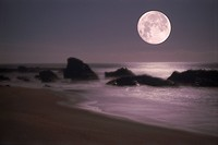 Full moon setting over wave painted sandy shore