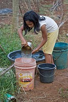 Crop irrigation, child filling buckets of water, used to hold irrigation water on vegetable farm, Palawan, Philippines, march
