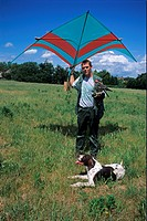 Falconry, falconer with colourful kite used to train falcons, German Wire_haired Pointer, England