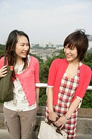 Two young women heartily share laughter as they stand against the railing