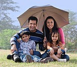 Family posing with an umbrella